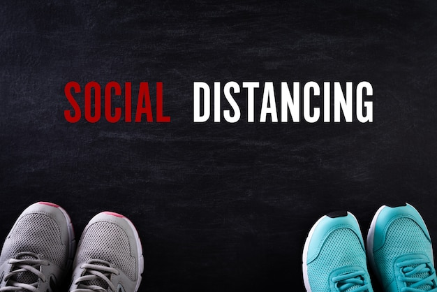 Twee schoenen voor sociaal afstandsconcept op zwarte muur