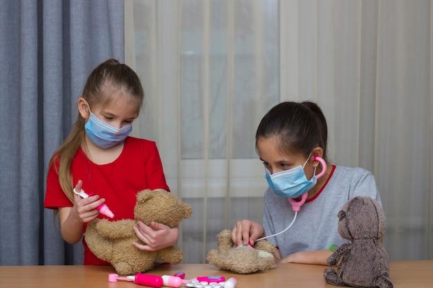 Twee schoolgaande meisjes spelen in het ziekenhuis met speelgoed voor medisch onderzoek