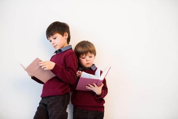 Twee schooljongens lezen boeken op een witte achtergrond in de studio.