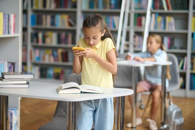Twee schoolkinderen die hun huiswerk maken in de bibliotheek
