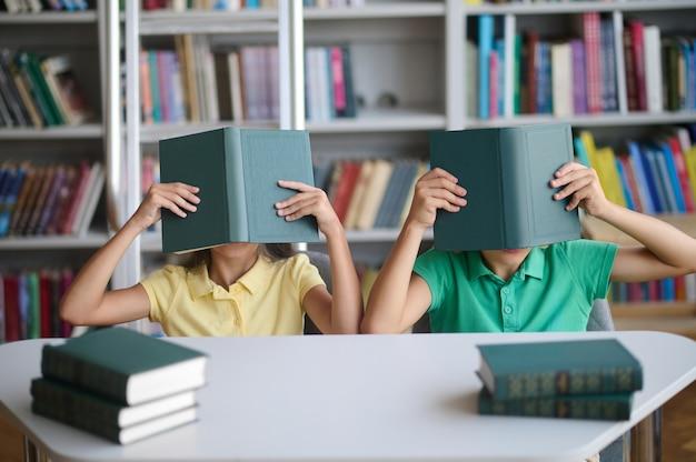 Twee schoolkinderen die plezier hebben in de bibliotheek
