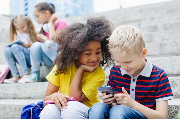 Twee schoolkinderen: een afrikaans-amerikaans meisje en een blonde jongen kijken naar een smartphone, zittend op de trap op een zonnige zomerdag buiten.