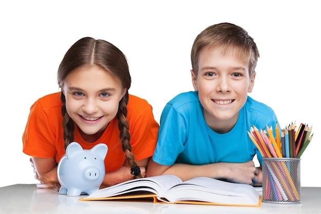 Twee schoolkinderen met spaarvarken en schoolboeken