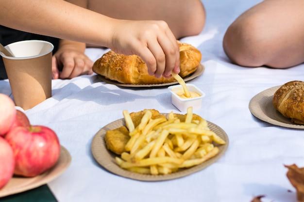 Twee schoolmeisjes eten friet met saus bij een picknick in het park. milieuvriendelijk wegwerpservies. schoolmaaltijden