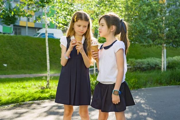 Twee schoolmeisjes in schooluniform die roomijs eten.