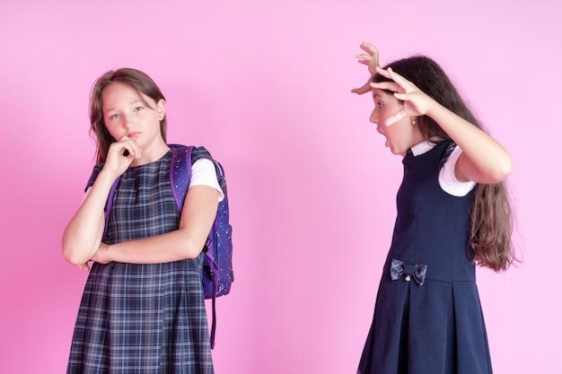 Twee schoolmeisjes maken ruzie op een roze achtergrond