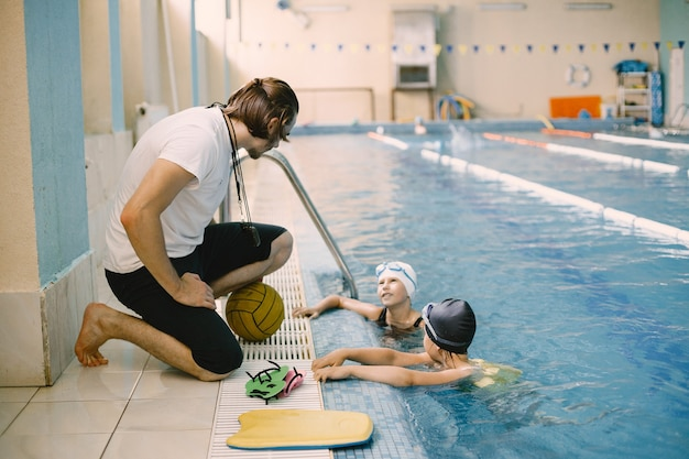 Twee schoolmeisjes waterpolospelers luisteren naar de leraar bij het zwembad. veel plezier, speel en spetter in een blauw zwembad