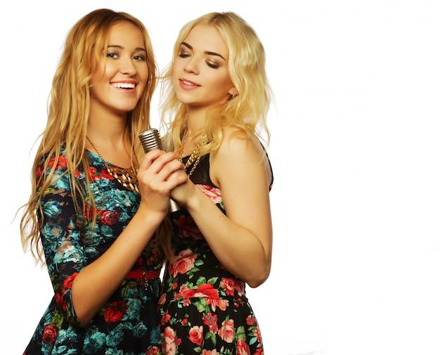 Twee schoonheid meisjes met een microfoon