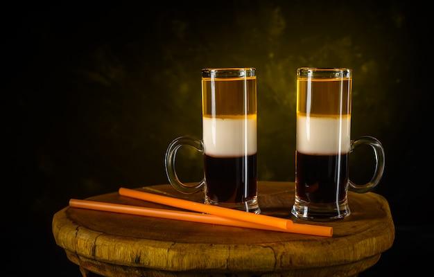 Twee schot b-52 cocktails en stro op houten uitstekend dienblad