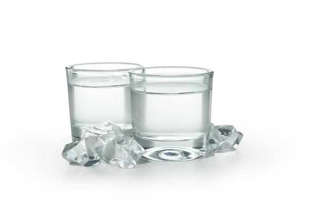 Twee schoten van wodka en ijsblokjes geïsoleerd op wit