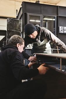 Twee schrijnwerkers controleren de kwaliteit van het werk op de werkplek