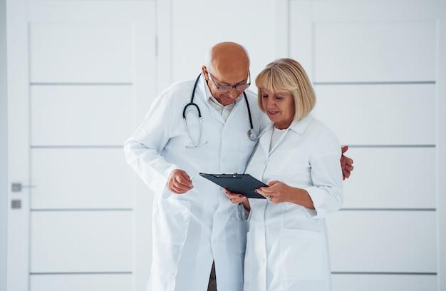 Twee senior artsen staan in de kliniek met kladblok en praten met elkaar.