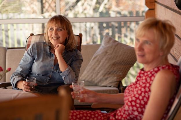 Twee senior female friends, vrouwen 55 jaar, houten patiohuis, lifestyle foto