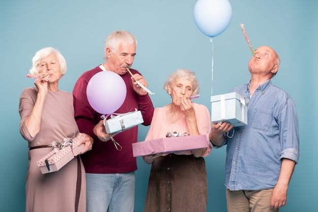 Twee senior koppels met geschenkdozen die fluitjes blazen terwijl ze verjaardagspret hebben