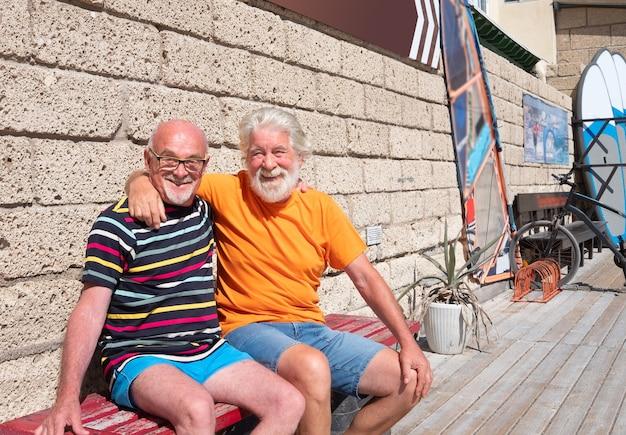Twee senior mannen met witte baard knuffelen elkaar en glimlachen. zittend op een houten bankje vlakbij de zee. surftafels en een fiets op de achtergrond