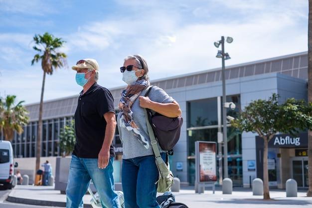 Twee senioren lopen met hun bagage en dragen een medisch masker om covid-19 of coronavirus of een ander type virus of ziekte te voorkomen - veilig reizigersconcept en levensstijl die buiten loopt