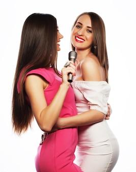 Twee sensuele meisjes zingen met microfoon, geïsoleerd op wit