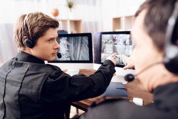 Twee serieuze mannen werken op kantoor aan beveiliging.