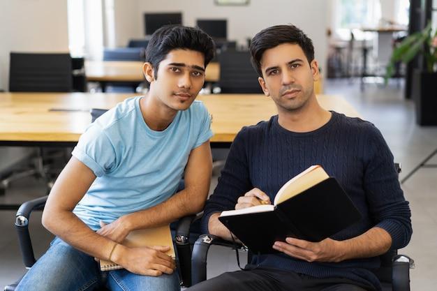 Twee serieuze medestudenten studeren en kijken naar de camera
