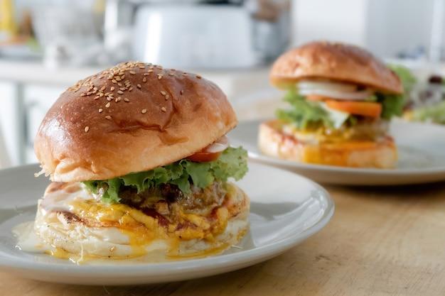 Twee sets hamburgers worden op een bord op een houten keukentafel gelegd.