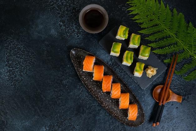 Twee sets sushi rolt met groenten en zeevruchten liggen op een zwarte achtergrond. bovenaanzicht