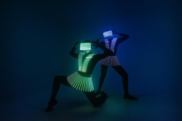 Twee sexy discodanseressen bewegen zich in uv-kostuums. feesten en dansen.