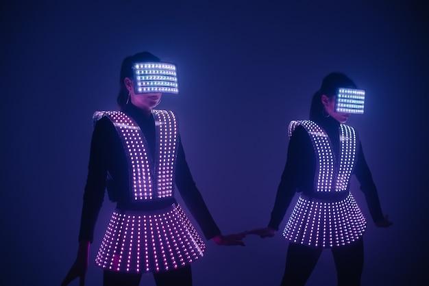 Twee sexy discodanseressen bewegen zich in uv-kostuums