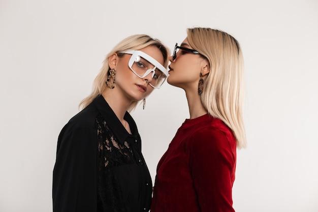 Twee sexy mooie jonge lesbiennes met blond haar in trendy bril in modieuze jurken staan are