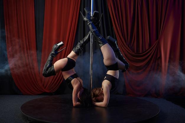 Twee sexy showgirls op het podium, paaldansdansers