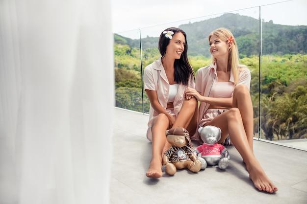 Twee sexy slanke vrienden: blond en brunette in pyjama met speelgoed draagt zittend balkon