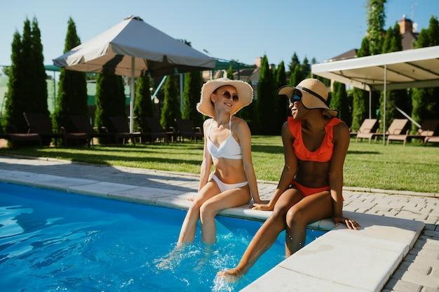 Twee sexy vriendinnen in zwemkleding poseren bij het zwembad