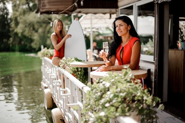 Twee sexy vrouwen met wakeboard het drinken champagne in in openlucht restaurant