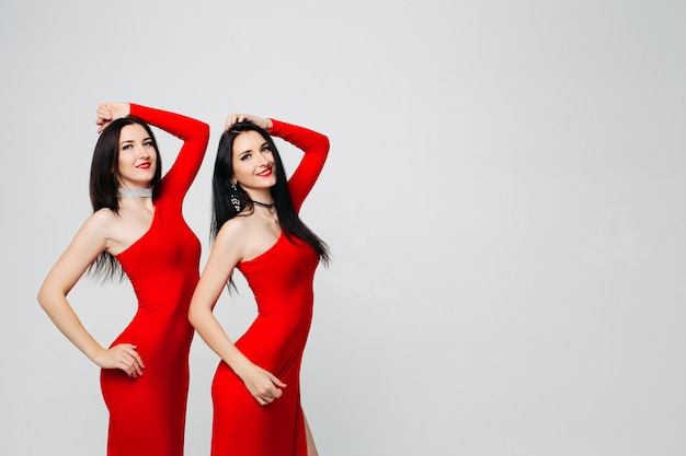 Twee sexy zusjes tweeling in rode jurken