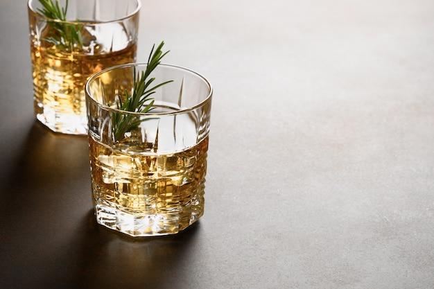 Twee shot whisky met ijsblokje op donker.