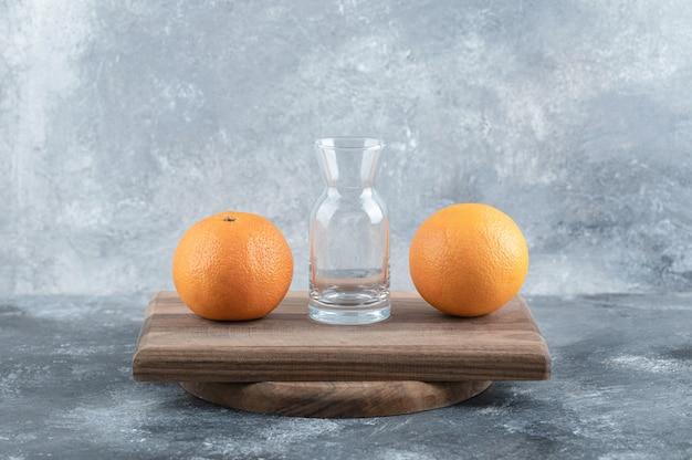 Twee sinaasappelen en glas op een houten bord.