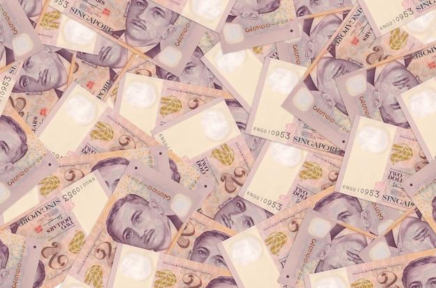 Twee singaporese dollarbiljetten liggen op een grote stapel