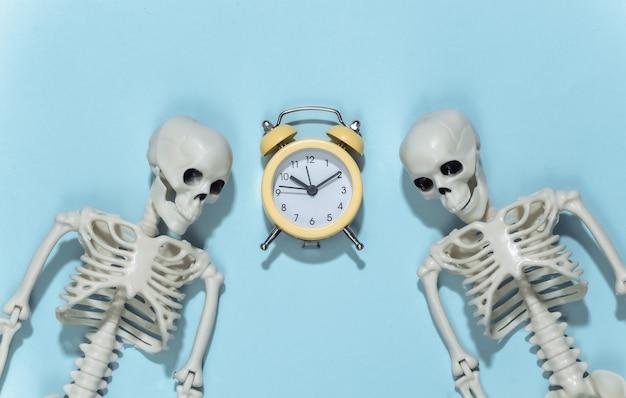 Twee skeletten en wekker op een blauwe achtergrond.