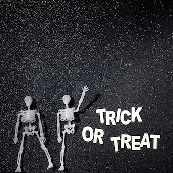 Twee skeletten in een trick or treat-compositie Gratis Foto