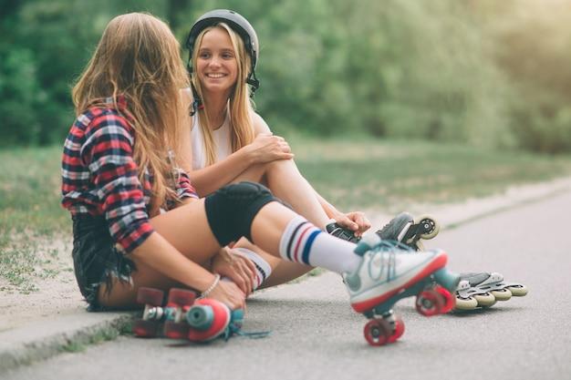 Twee slanke en sexy jonge vrouwen en rolschaatsen. een vrouwtje heeft een inline skates en de andere heeft een quad skates. meisjes rijden in de stralen van de zon.