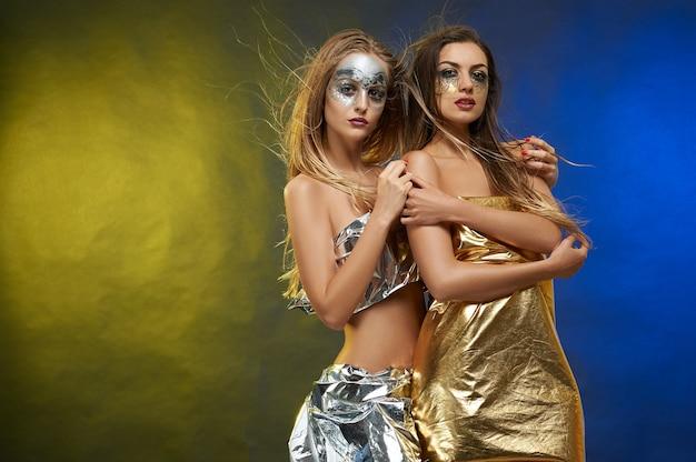 Twee slanke meisjes met artistieke make-ups.