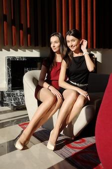 Twee slanke vrouwen met lange benen in beige panty's en stiletto's