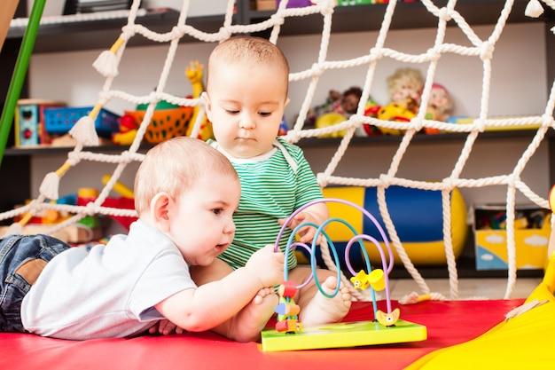 Twee slimme jongensbaby's die met speelgoed in speelkamer spelen