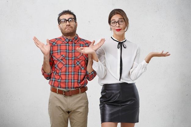 Twee slimme mensen halen hun schouders op en gebaren met hun handen, zeg maar who cares