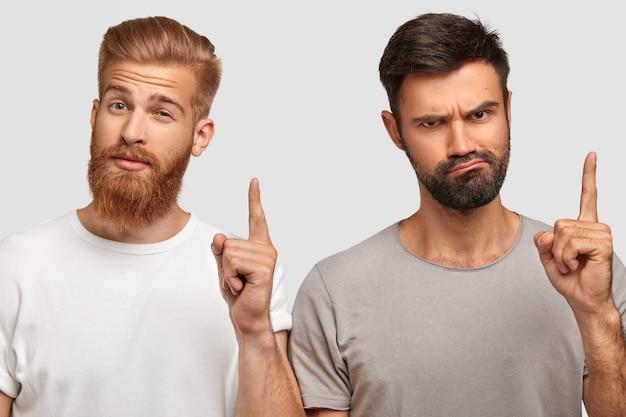 Twee slimme studenten met serieuze uitdrukkingen, steek de wijsvinger op, hebben een leuk idee voor projectwerk