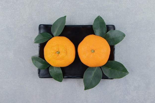 Twee smakelijke clementinevruchten op zwarte plaat
