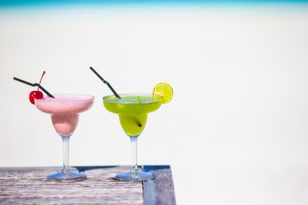 Twee smakelijke cocktails op tropisch wit strand