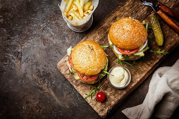 Twee smakelijke gegrilde klassieke rundvleesburgers met frietjes op een rustieke zwarte tafelbladweergave met kopie ruimte