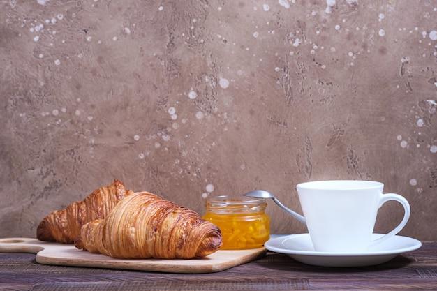 Twee smakelijke klassieke croissant en koffie cappuccino op tafel