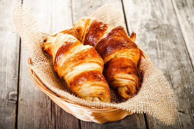 Twee smakelijke oliecroissants in mand die op oude houten lijst ligt