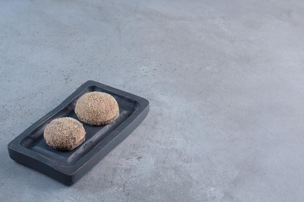 Twee smakelijke truffelballen geplaatst op zwarte plaat.